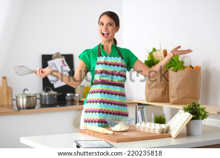 Smiling young woman in the kitchen, isolated on background - stock photo