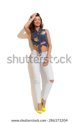 Smiling young woman in torn jeans leaning on white wall in the sunlight. Full length studio shot on white background. - stock photo