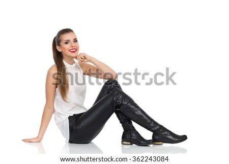 Smiling young woman in white shirt, black leather trousers and boots sitting on a floor and holding hand on chin. Full length studio shot isolated on white - stock photo