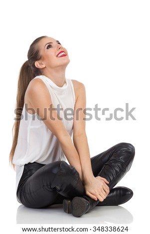 Smiling young woman in white shirt, black leather trousers and boots sitting on a floor with legs crossed, and looking at camera. Full length studio shot isolated on white.
