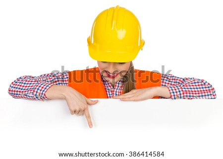 Smiling young woman in yellow hardhat, orange reflective vest and lumberjack shirt posing behind big white poster, looking down and pointing. Studio shot isolated on white. - stock photo