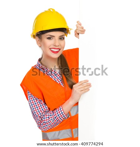 Smiling young woman in yellow hardhat, orange reflective vest and lumberjack shirt standing behind big white banner and holding it. Waist up studio shot isolated on white. - stock photo