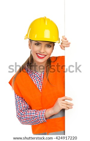 Smiling young woman in yellow hardhat, orange reflective vest and lumberjack shirt standing behind big white banner, holding it and looking at camera. Waist up studio shot isolated on white. - stock photo