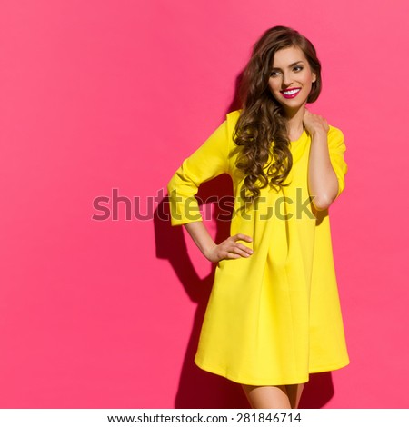 Smiling young woman in yellow mini dress posing against pink background and looking away at copy space. Three quarter length studio shot. - stock photo