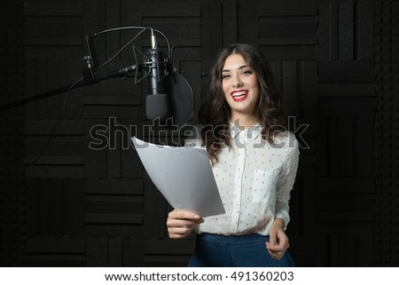 Smiling young woman inside recording station
