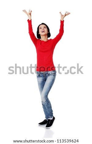 Smiling young woman  is holding something abstract above her head. Happy girl with raised hands. Isolated on white background. - stock photo