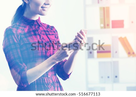 Smiling young woman is looking at her smartphone screen while standing in office with bookshelf and binders. Toned image