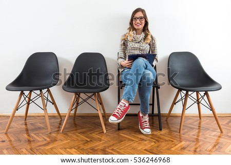 Smiling young woman is sitting in a waiting room. She is ready for the job interview.