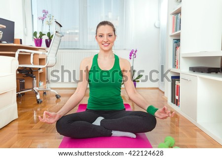 Smiling young woman is sitting on the floor at home doing yoga meditation. - stock photo