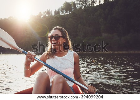 Smiling young woman kayaking on a lake. Happy young woman canoeing in a lake on a summer day.