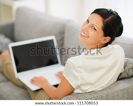 Smiling young woman laying on couch and working on laptop