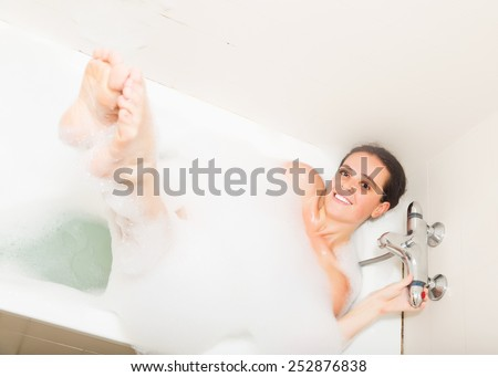 Smiling young woman laying with foam in bath