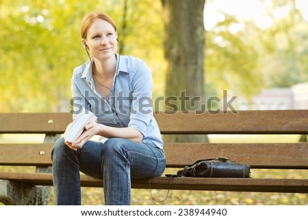 Smiling young woman listens to music on a smartphone and holds a book in her hands while sitting on a bench in a city park. - stock photo