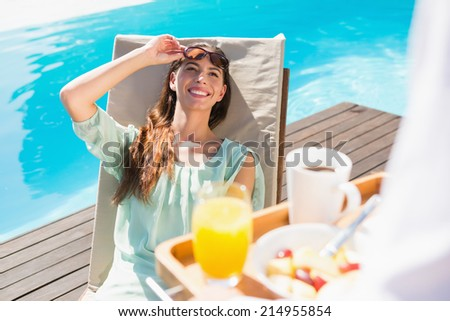 Smiling young woman looking at cropped waiter with breakfast tray by the pool - stock photo