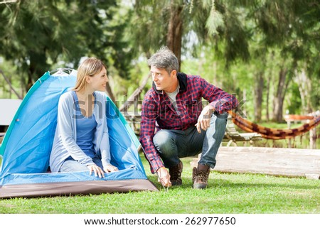 Smiling young woman looking at man preparing tent in park - stock photo