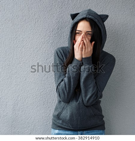 Smiling young woman looking away while covering mouth with hands. - stock photo