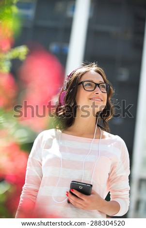 Smiling young woman looking away while listening music outdoors - stock photo