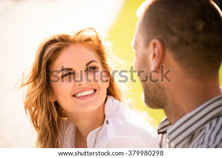 Smiling young woman looking to eyes of her man on date outdoors - stock photo