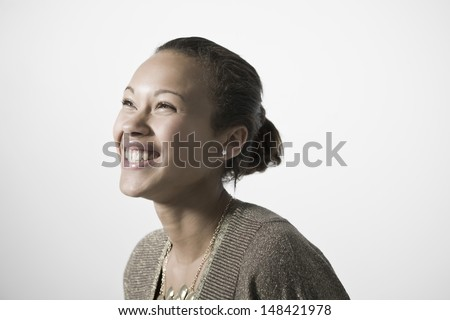 Smiling young woman looking up against gray background - stock photo