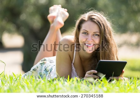 Smiling young woman lying on grass in meadow and reading ereader  - stock photo
