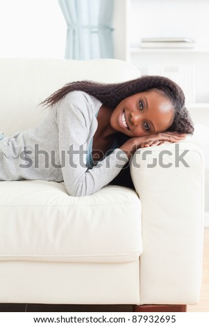 Smiling young woman lying on the couch