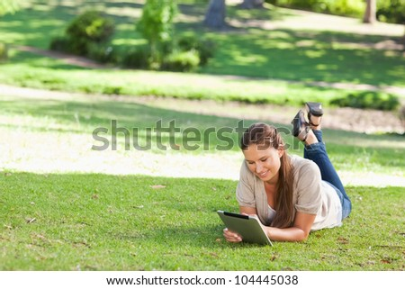 Smiling young woman lying on the lawn with a tablet computer - stock photo
