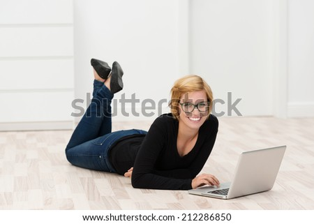 Smiling young woman lying relaxing on the wooden floor with her feet in the air working on a laptop computer in a white painted room - stock photo