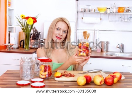 Smiling young woman making canned peaches - stock photo