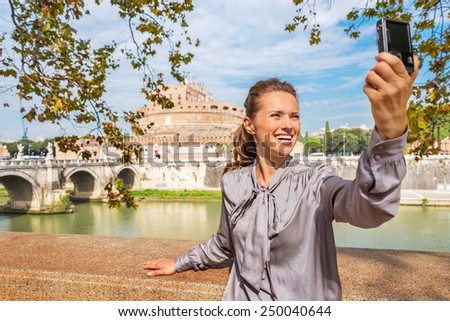 Smiling young woman making selfie on embankment near castel sant'angelo in rome italy - stock photo