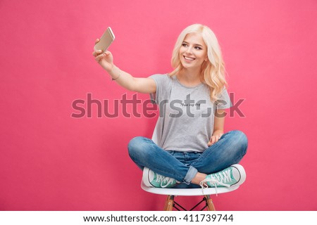 Smiling young woman making selfie photo on smartphone over pink background - stock photo