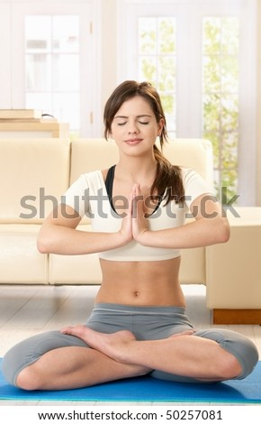 Smiling young woman meditating on blue floor mat in living room with closed eyes.