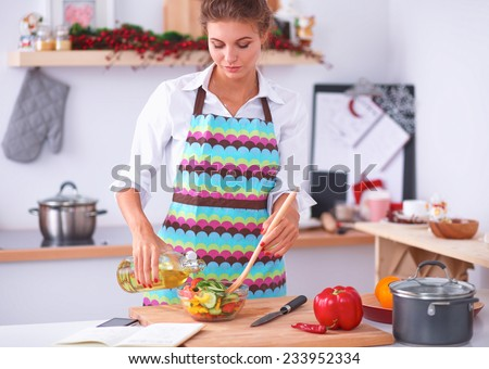 Smiling young woman  mixing fresh salad - stock photo