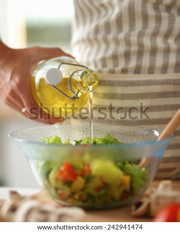Smiling young woman  mixing fresh salad, holding bottle of oil - stock photo