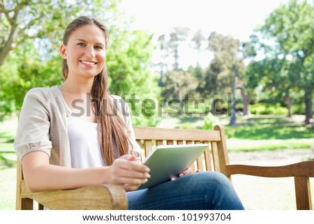 Smiling young woman on a bench in the park with her tablet computer