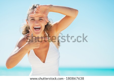 Smiling young woman on beach framing with hands - stock photo