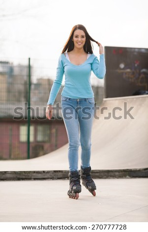 Smiling young woman on rollerblades in a skate park - stock photo
