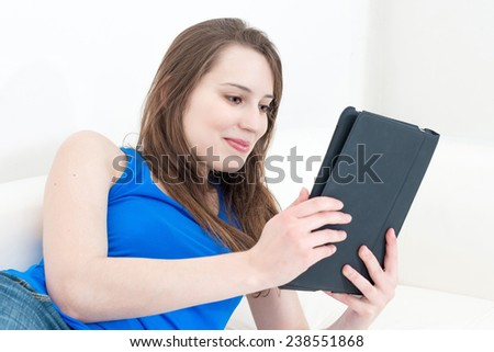 Smiling young woman on the couch with her tablet