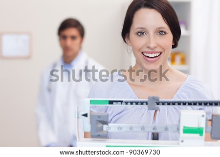 Smiling young woman on the scale