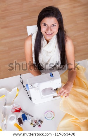 Smiling young woman or seamstress working with her sewing machine stitching a long length of fabric