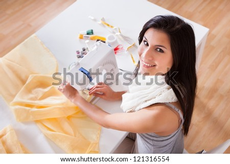 Smiling young woman or seamstress working with her sewing machine stitching a long length of fabric - stock photo