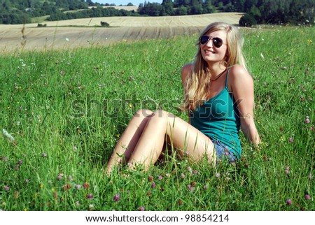 smiling young woman outdoors in summer - stock photo