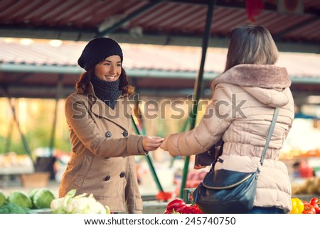 Smiling young woman paying for vegetables at market - stock photo