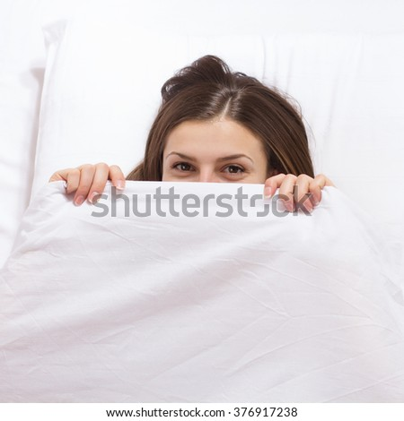 Smiling young woman, peeking under the covers, fully rested female, in the morning after sleeping. - stock photo