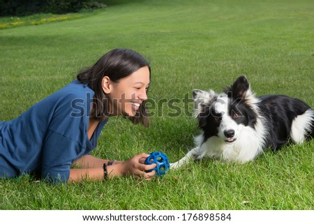 Smiling young woman playing with her border collie in the park - stock photo