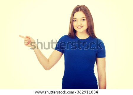 Smiling young woman pointing aside.