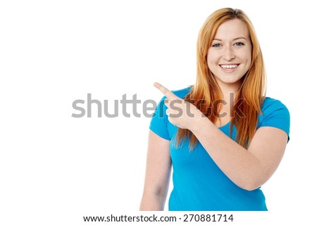 Smiling young woman pointing at copy space