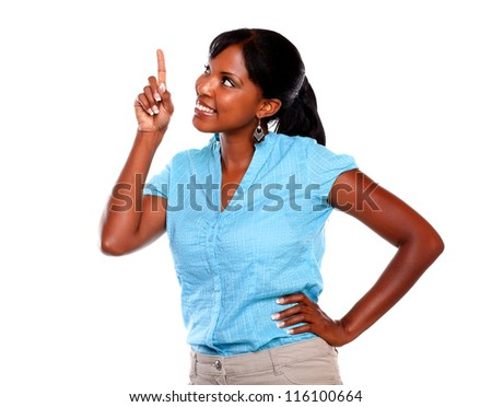 Smiling young woman pointing up on blue shirt against white background - copyspace - stock photo
