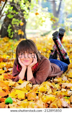 Smiling young woman portrait lying on her stomach in autumn park and looking at camera. - stock photo