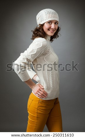 Smiling young woman posing in a studio wearing a sweater and crochet hat on gray background - stock photo