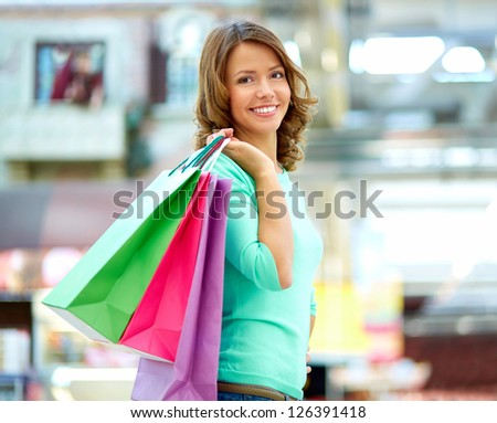 Smiling young woman posing with a handful of shopping bags - stock photo